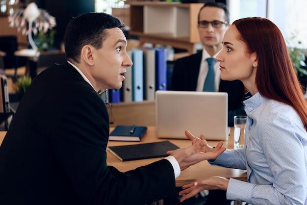 Rote vorangegangene frau argumentiert mit erwachsenem mann im scheidungsbüro.