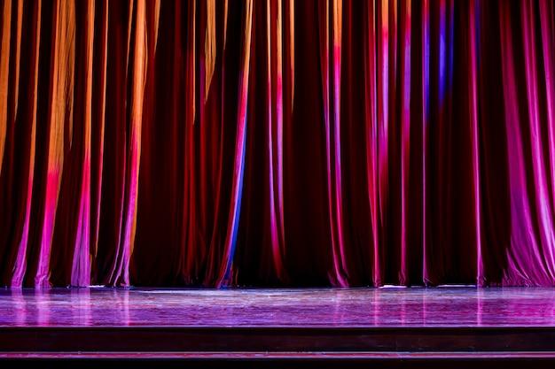 Rote vorhänge und der scheinwerfer im theater zwischen shows.