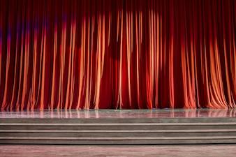 Rote Vorhänge und Bühne aus Holz.