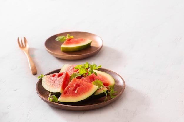 Rote wassermelone auf einem holzteller geschnitten