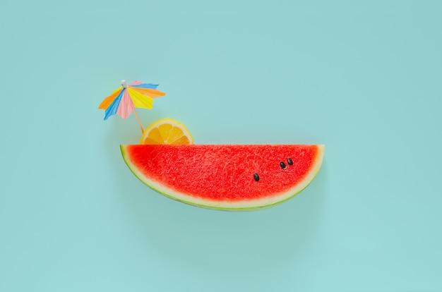 Rote wassermelone mit zitronenscheibe und cocktailschirm auf blauem hintergrund. minimales sommergetränkekonzept.