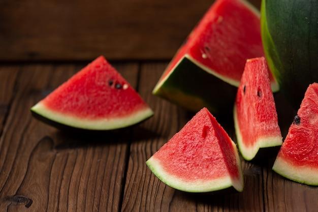 Rote wassermelonenscheibe auf holzhintergrund