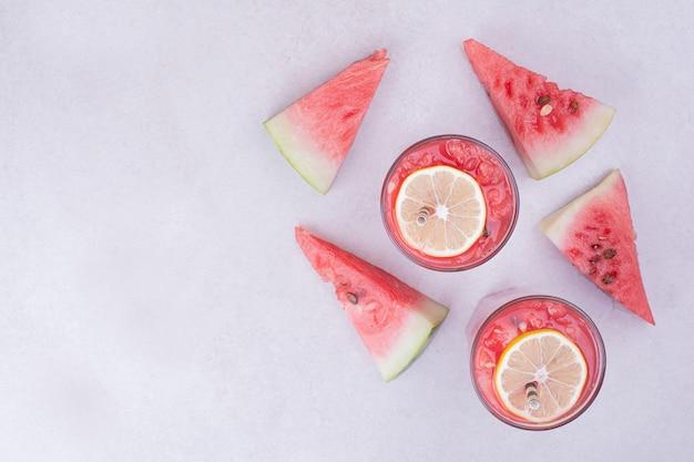 Rote wassermelonenscheiben mit zwei gläsern saft