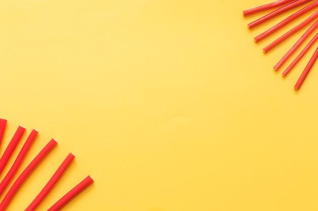 Rote weiche süßholzsüßigkeiten auf gelbem hintergrund