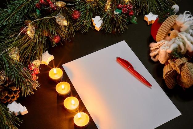 Rote weihnachtsbälle und notizbuch, die nahe grüner fichtenniederlassung auf draufsicht des schwarzen hintergrundes liegen. platz kopieren. stillleben. flach liegen. neujahr