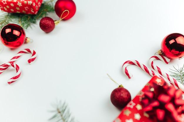 Rote weihnachtsdekoration auf weißem hintergrund, weihnachtsgeschenke, süßigkeiten, lutscher. foto in hoher qualität