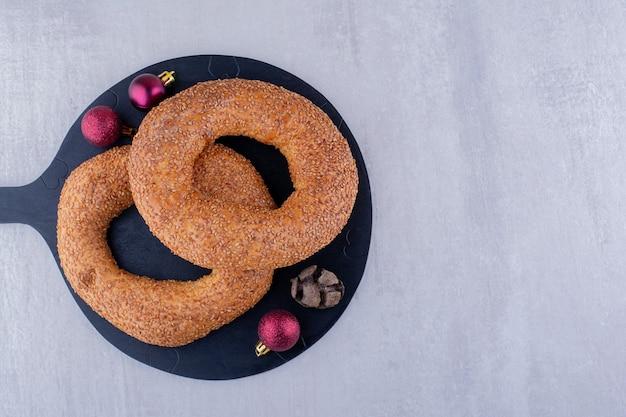 Rote weihnachtsdekoration, zypressenkegel und mit sesam beschichtete bagels auf einer schwarzen tafel auf weißem hintergrund.