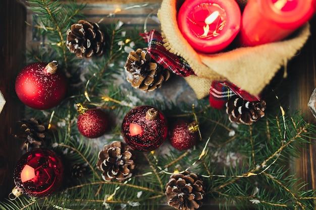 Rote weihnachtsdekorationen auf dem tisch am verschwommenen weihnachtsbaum mit kerzen. foto in hoher qualität