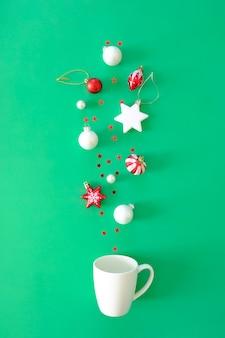 Rote weihnachtselemente fallen in eine weiße tasse auf einer grünen oberfläche