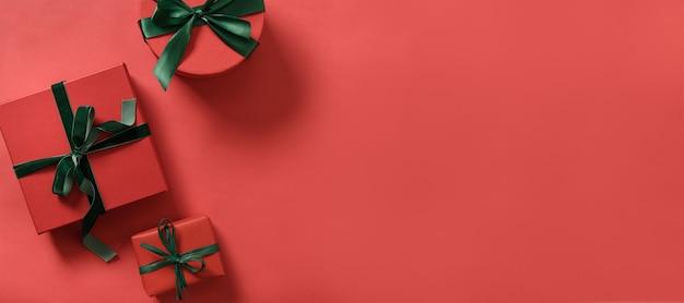 Rote weihnachtsgeschenke und grünes band auf roter oberfläche.