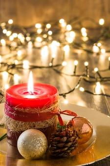 Rote weihnachtskerze und weihnachtsverzierungen auf holz