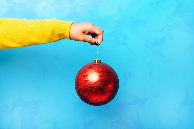 Rote weihnachtskugel in der hand über blauem, fröhlichem weihnachtskonzept