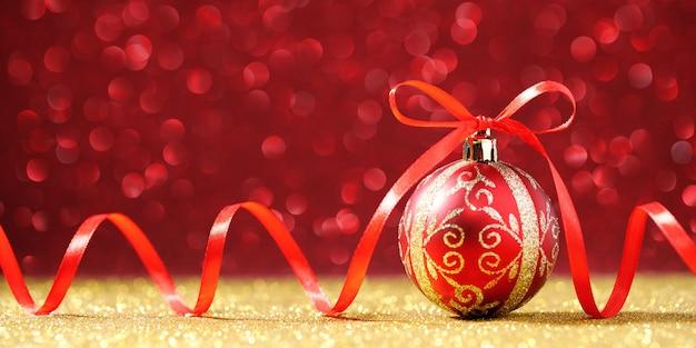Rote weihnachtskugel mit bogen auf glitzerhintergrund