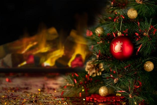 Rote weihnachtskugel mit simbol des neuen jahres auf einem tannenbaum. kamin in unscharfem hintergrund. weihnachtsfeiertagshintergrund mit kopienraum. abstrakte unschärfe. weicher fokus