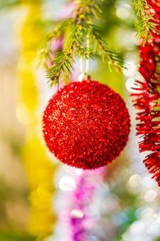 Rote weihnachtskugel und leuchtendes lametta hängen am ast des baumfokus im vordergrund verschwommenes bokeh