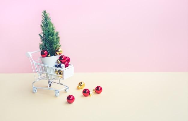 Rote weihnachtskugel und verzierung auf wagen, wagen auf pastellfarbe