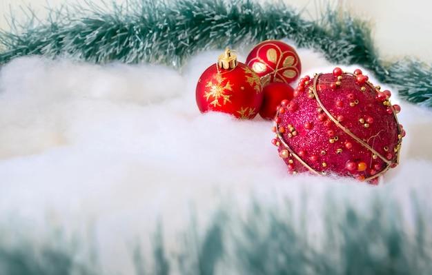 Rote weihnachtskugeln auf künstlichem schnee und weihnachtsbaum branchs
