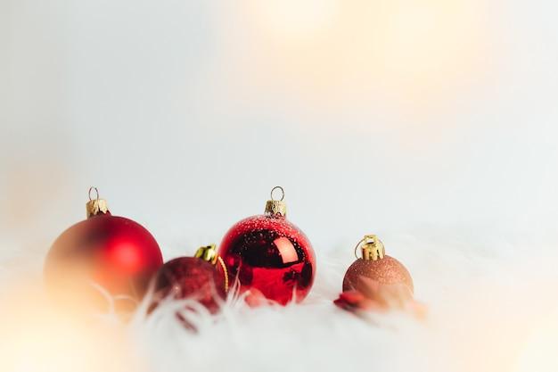 Rote weihnachtskugeln auf weißem hintergrund mit federn