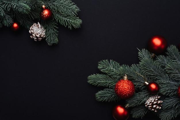 Rote weihnachtskugeln auf zweigen eines weihnachtsbaumes auf einem schwarzen hintergrund.