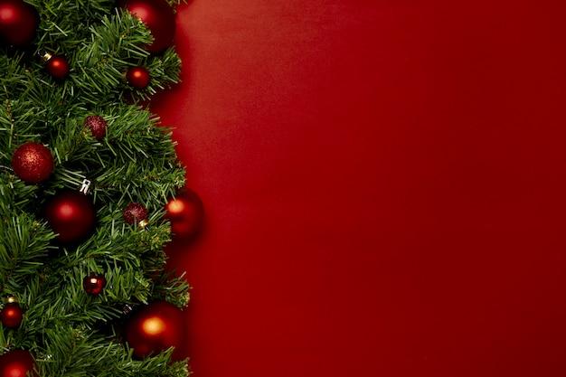 Rote weihnachtskugeln dekoration auf rotem hintergrund mit textfreiraum