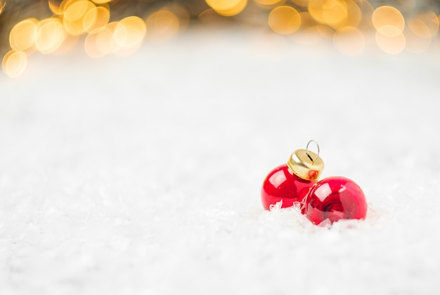 Rote weihnachtskugeln, die auf dem schnee auf dem hintergrund des weihnachtsbaumes liegen