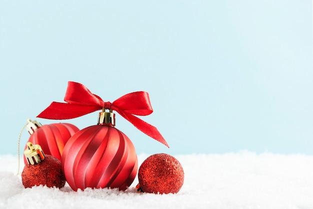 Rote weihnachtskugeln, flitter auf schnee, wenn das rote farbband getrennt ist.