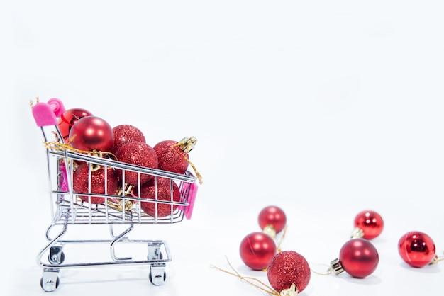 Rote weihnachtskugeln in kleiner einkaufskarte,