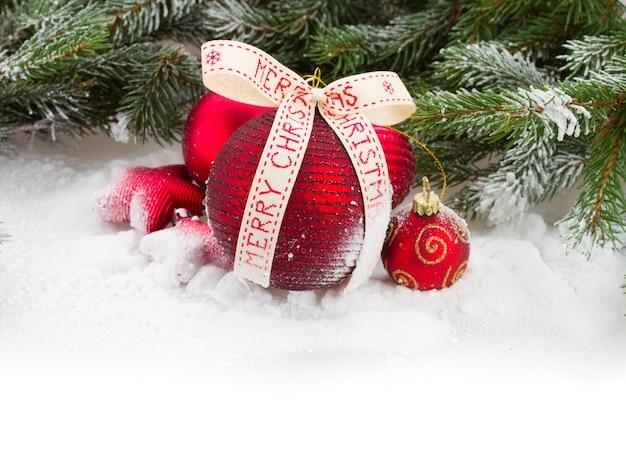 Rote weihnachtskugeln mit fröhlichem weihnachtsbogen auf weißem schnee