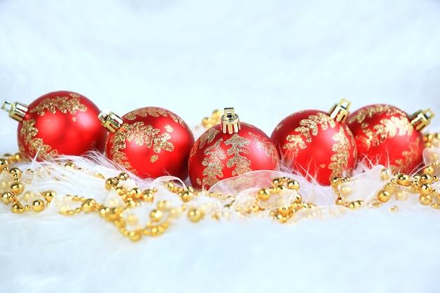 Rote weihnachtskugeln mit schnee lokalisiert auf weiß