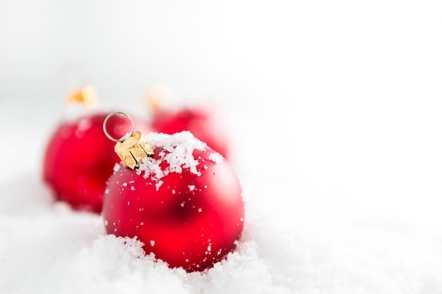 Rote weihnachtskugeln mit schnee