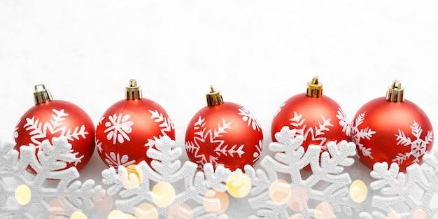 Rote weihnachtskugeln mit schneeflocken auf weißem hintergrund und goldenen lichtern
