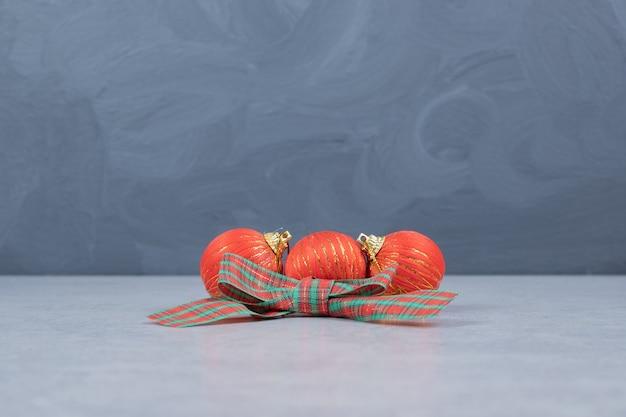 Rote weihnachtskugeln und -band auf grauem hintergrund. hochwertiges foto