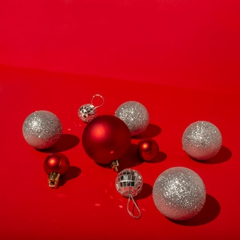 Rote weihnachtskugeln und discokugeln auf rotem tisch