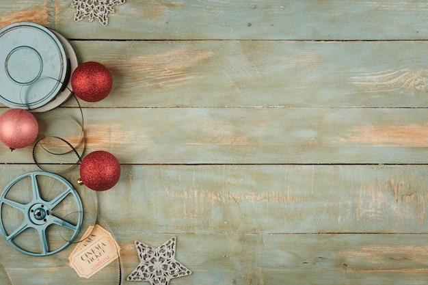 Rote weihnachtskugeln und kinoobjekte auf hölzernem hintergrund