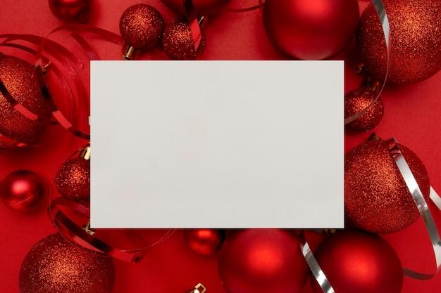Rote weihnachtskugeln und leere karte auf rotem tisch