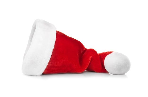 Rote weihnachtsmannmütze auf weißer fläche