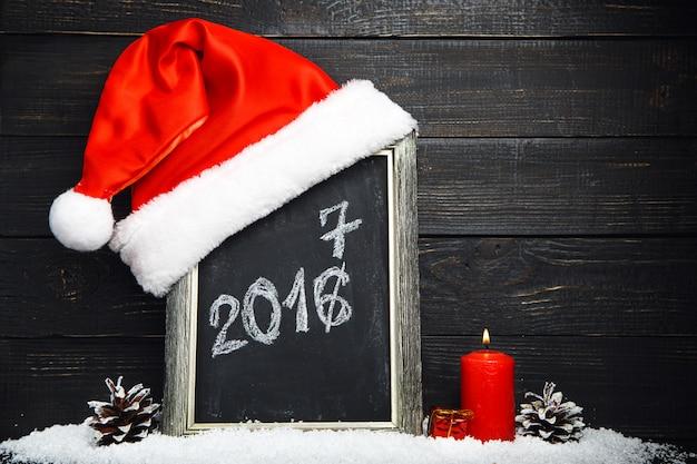 Rote weihnachtsmütze auf der tafel mit schnee