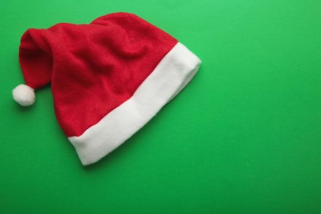 Rote weihnachtsmütze auf grünem hintergrund mit kopienraum. ansicht von oben