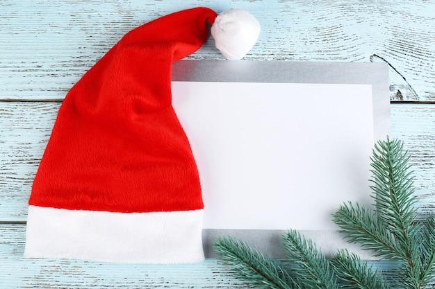 Rote weihnachtsmütze mit tannenzweig und karte auf farbigem holztisch