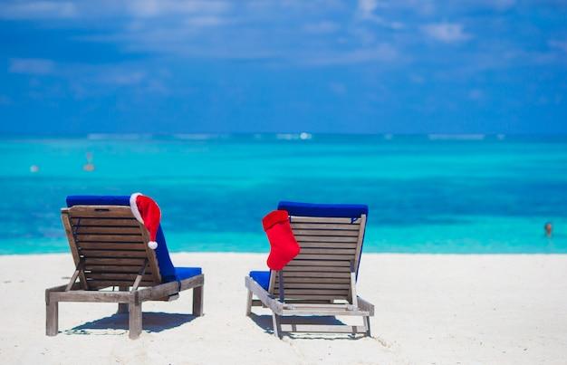 Rote weihnachtsmütze und roter weihnachtsstrumpf auf strandruhesesseln auf tropischen ferien