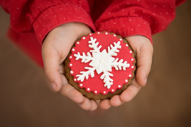 Rote weihnachtsplätzchen mit schneeflocke, die hände halten