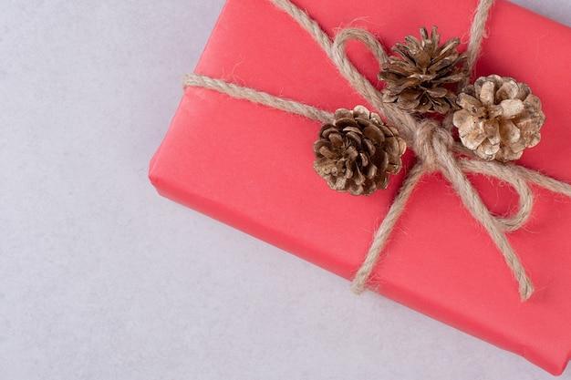 Rote weihnachtsschachtel mit drei tannenzapfen auf weiß.