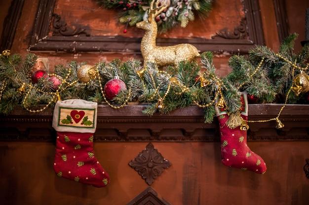 Rote weihnachtssocke, die am kamin hängt. fichtenzweige, spielzeug weihnachtsstimmung