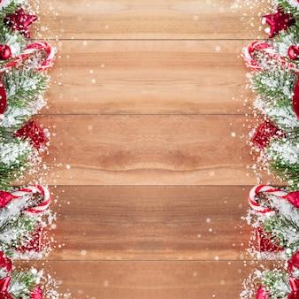 Rote weihnachtsverzierungen mit der kiefer und schnee verziert auf täfelungshintergrund