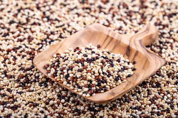 Rote, weiße und braune quinoa-oberfläche mit einem holzlöffel.