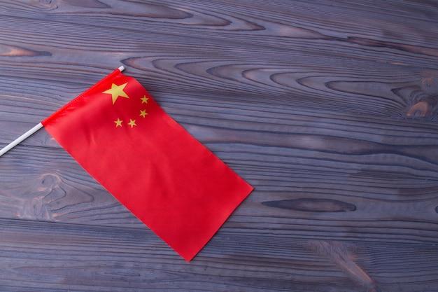 Rote wellenflagge von china auf grauem hölzernem schreibtischhintergrund