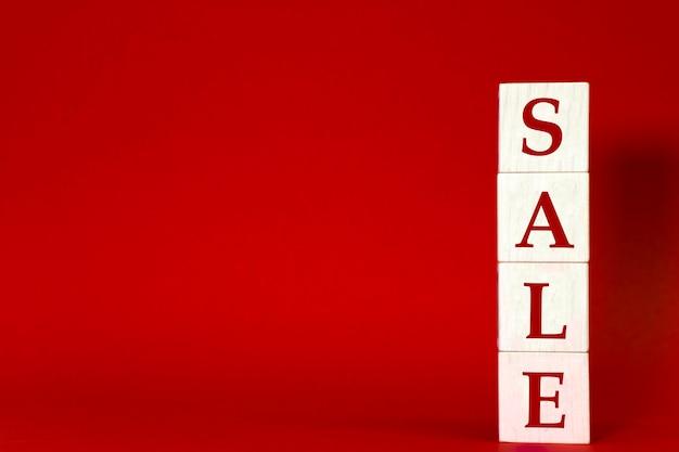 Rote werbevorlage mit verkaufswort aus holzklötzen für rabatt-werbebanner. speicherplatz kopieren.