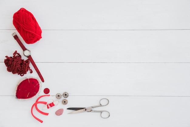 Rote wolle; armbanduhr; schere; faden; nadelkissen mit nadel auf weißem holztisch