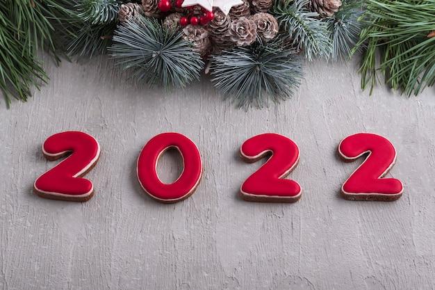 Rote zahl 2022 aus lebkuchen und weihnachtskranz. gute neujahrsstimmung. hellgraue wand im hintergrund.