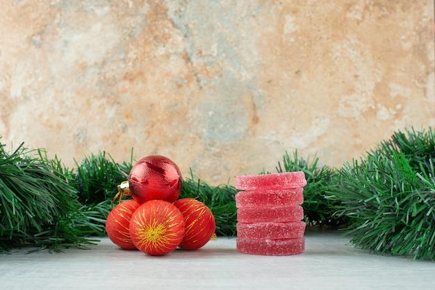 Rote zuckermarmelade mit roten weihnachtskugeln auf marmorhintergrund. hochwertiges foto